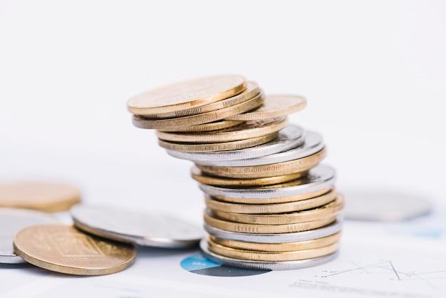 Gefallener stapel münzen auf weißem hintergrund über dem diagramm Kostenlose Fotos