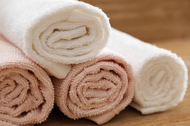 Gefaltete badetücher rosa und weiß gefärbt auf holztisch für hotelbadekurort. flauschige handtücher reinigen. nahansicht. Premium Fotos