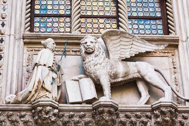 Geflügelter löwe und ein priester, detail des dogenpalastes palazzo ducale in venedig, italien, Premium Fotos
