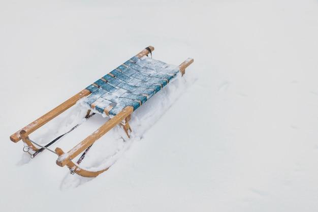 Gefrorener hölzerner schlitten auf schneebedecktem land an der wintersaison Kostenlose Fotos