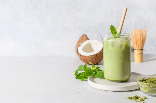 Gefrorener latte grüner matcha-tee mit kokosmilchgarniturminze auf weißem hintergrund. Premium Fotos