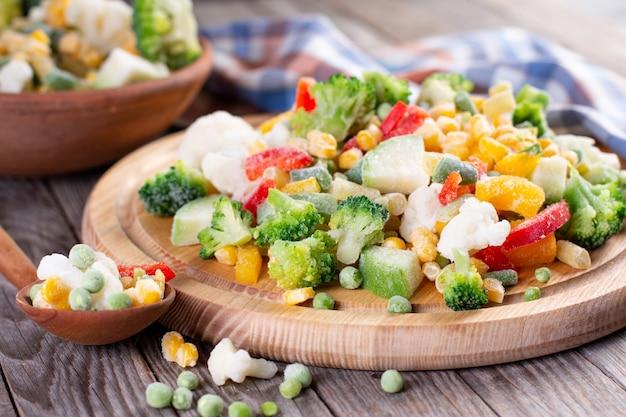 Gefrorenes gemüse auf holzbrett auf tisch Premium Fotos