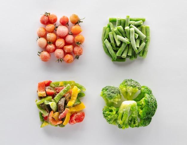 Gefrorenes gemüse auf weißem hintergrund. kirschtomaten, grüne bohnen, paprika und brokkoli werden in quadraten ausgelegt. Premium Fotos