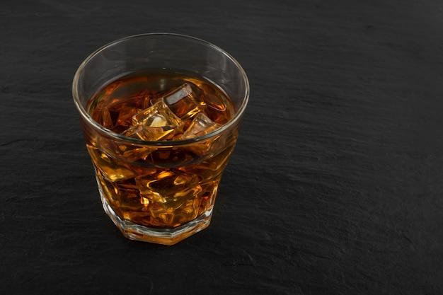 Gefrorenes whisky-glas auf natürlichem schwarzem steinhintergrund Premium Fotos