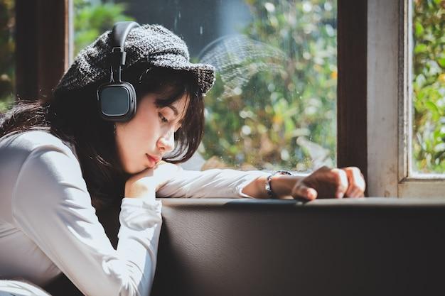Gefühl, das trauriges hören des jungen mädchens zur musik schauend das fenster glaubt Premium Fotos