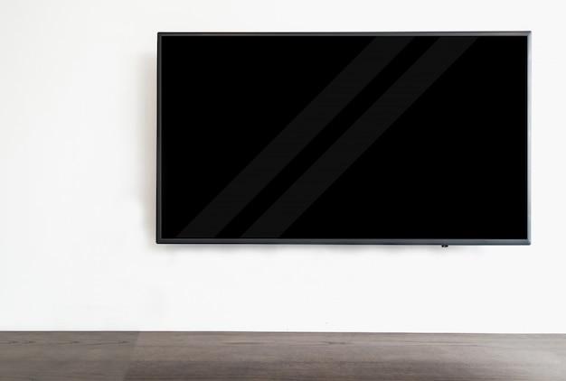 Geführtes intelligentes fernsehen, das am weißen wandhintergrund, mit hölzerner tabelle hängt. Premium Fotos