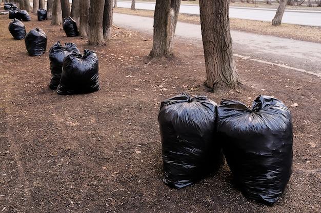 Gefüllt mit schwarzen plastiktüten des abfalls in der natur, in einem allgemeinen park, entlang der straße. Premium Fotos