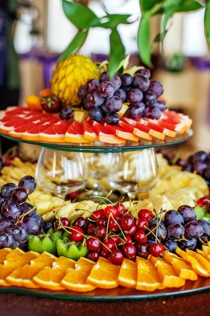 Gefüllte früchte mit orangen, kiwis, trauben, kirschen und ananas Premium Fotos