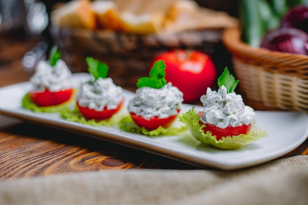 Gefüllte tomatenscheiben von der seite mit frischkäse und kräutern Kostenlose Fotos