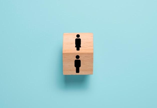 Gegenüber mann und frau ikone auf holzblockwürfel. mann und frau denken und verhalten sich ganz unterschiedlich. Premium Fotos
