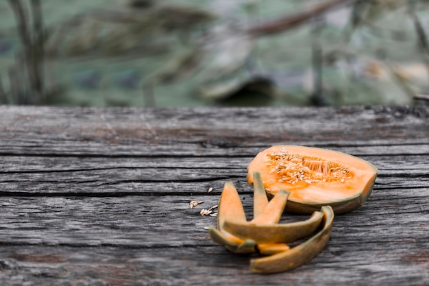 Gegessene und halbierte moschusmelone auf verwittertem holztisch Kostenlose Fotos