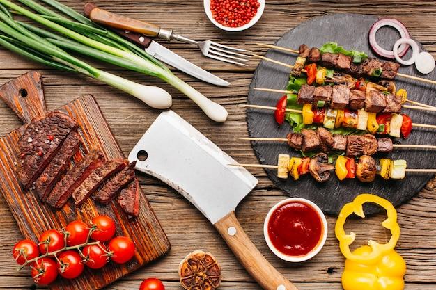 Gegrillte fleischaufsteckspindeln und -steak mit gemüse auf hölzernem schreibtisch Kostenlose Fotos