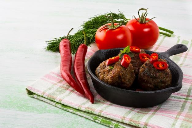 Gegrillte fleischbällchen mit chili-pfeffer-scheiben in einer gusseisernen pfanne Premium Fotos