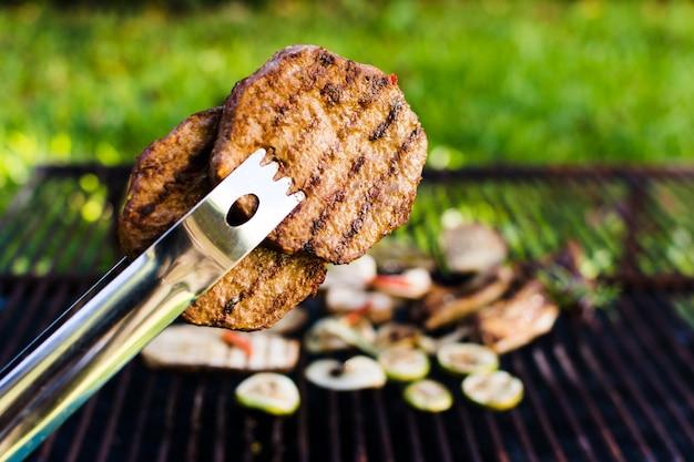 Gegrillte fleischpastetchen in der zange draußen auf picknick Kostenlose Fotos