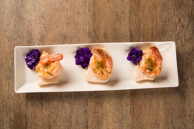 Gegrillte garnelen mit rohem nagelfisch auf weißem teller am tisch Premium Fotos