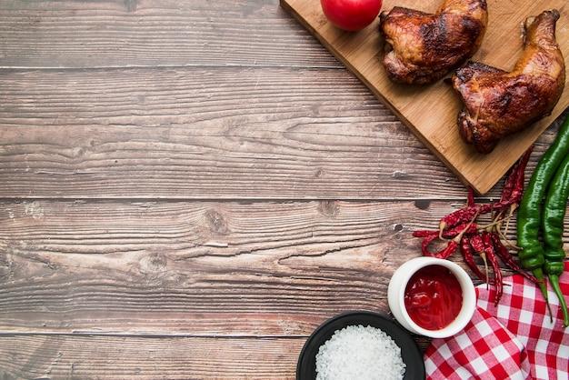 Gegrillte gebratene hühnerkeule mit chilischoten; salz; sauce und serviette auf dem schreibtisch Kostenlose Fotos