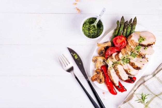Gegrillte hähnchenbrust auf einem teller mit tomaten, spargel und champignons auf einem teller, flach legen Premium Fotos