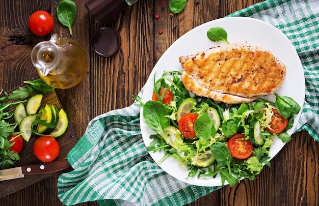 Gegrillte hähnchenbrust und frischer gemüsesalat - tomaten, gurken und salatblätter. hühnchensalat. gesundes essen. flach liegen. ansicht von oben Kostenlose Fotos
