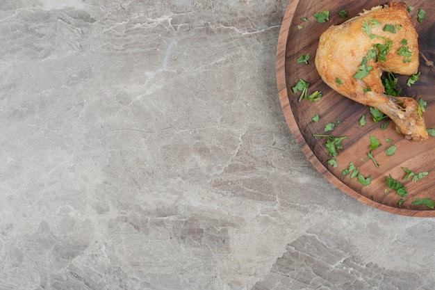 Gegrillte hähnchenkeule auf holzteller. Kostenlose Fotos