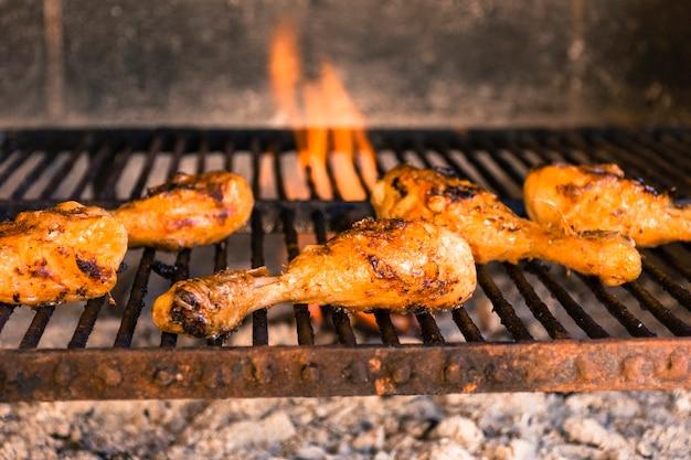 Gegrillte hühnerbeine auf heißem grill mit schwerem feuer Kostenlose Fotos