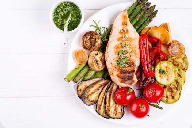 Gegrillte hühnerbrust auf einer platte mit grillgemüse auf platte, flache lage Premium Fotos