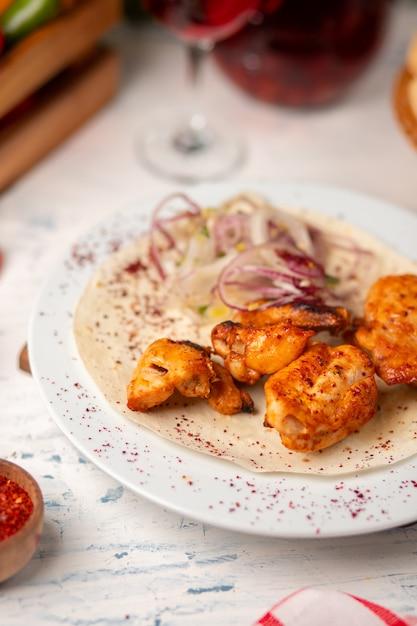 Gegrillte hühnernuggets, flügel, brust mit zwiebelsalat Kostenlose Fotos