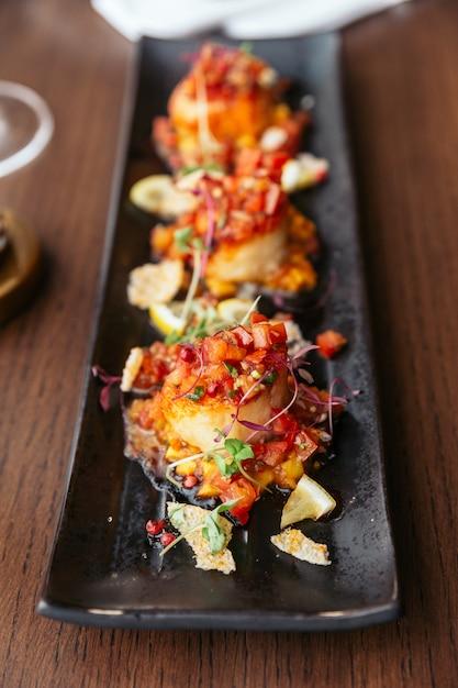 Gegrillte jakobsmuscheln mit süßer und saurer salsa-salsa. Premium Fotos