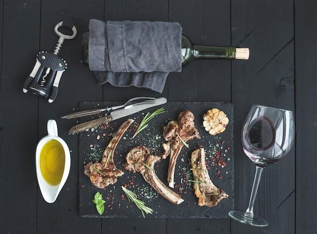 Gegrillte lammkoteletts. lammkarree mit knoblauch, rosmarin, gewürzen auf schieferblech, weinglas, öl in einer untertasse, korkenzieher und flasche über schwarzer hölzerner tabelle Premium Fotos