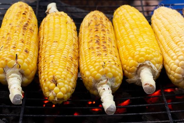 Gegrillte maiskolben auf dem heißen herd mit holzkohle Premium Fotos