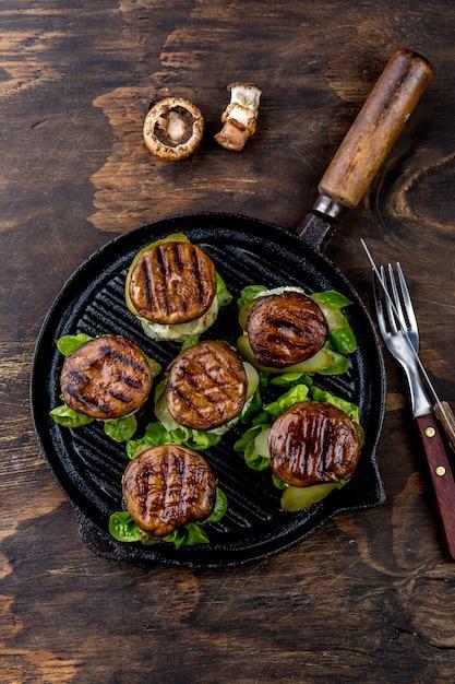 Gegrillte portobello brötchenpilzburger auf roheisengrillwanne ob hölzern, draufsicht Premium Fotos