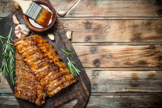 Gegrillte rippchen mit rosmarin, gewürzen und sauce. auf einem hölzernen hintergrund. Premium Fotos