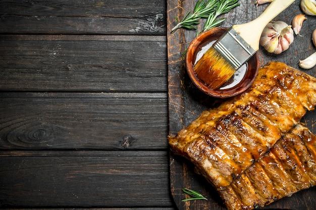 Gegrillte rippchen mit sauce, kräutern und gewürzen. Premium Fotos