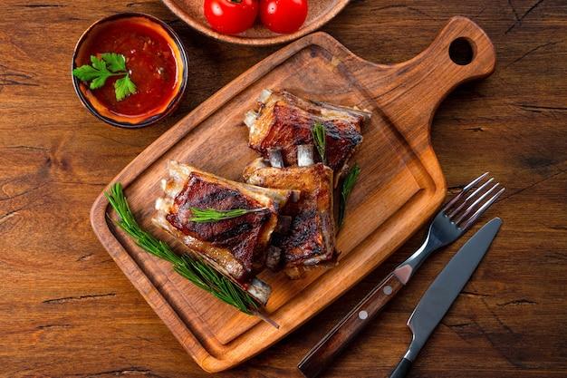Gegrillte rippen in barbecue-sauce auf dem schneidebrett Premium Fotos