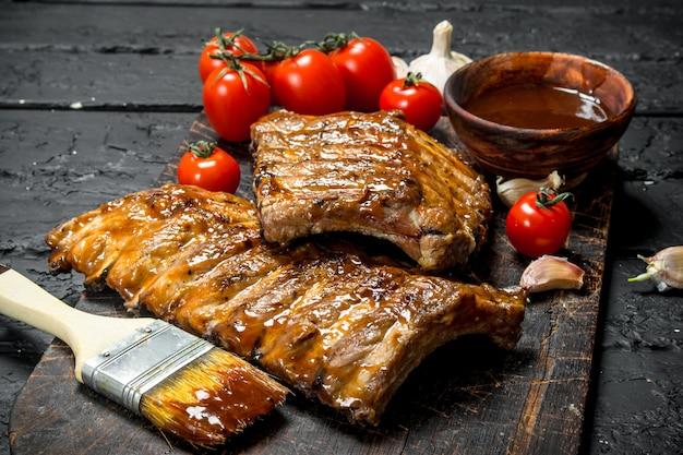 Gegrillte rippen mit sauce auf dunklem rustikalem tisch. Premium Fotos