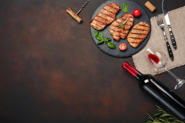Gegrillte schweinefleischsteaks auf stein mit flasche wein, weinglas, messer und gabel auf rostigem hintergrund Premium Fotos