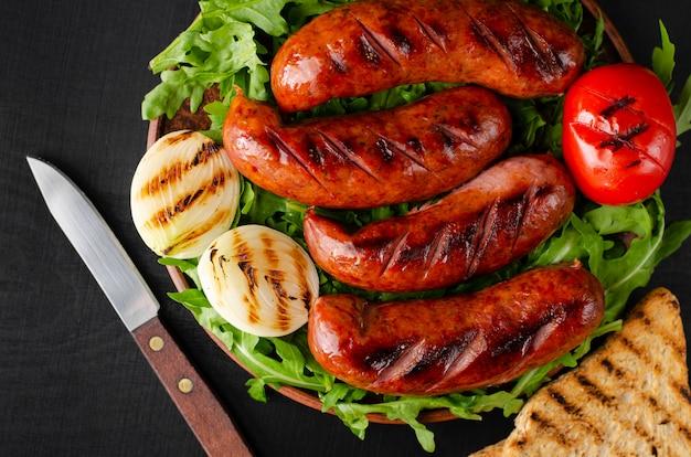 Gegrillte schweinefleischwürste mit arugula und gemüse auf schwarzem hintergrund. nahaufnahme, überholter schuss. Premium Fotos