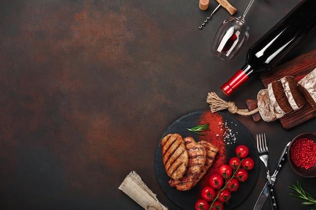 Gegrillte schweinesteaks mit flasche wein, weinglas, messer, gabel, schwarzbrot, kirschtomaten und rosmarin Premium Fotos