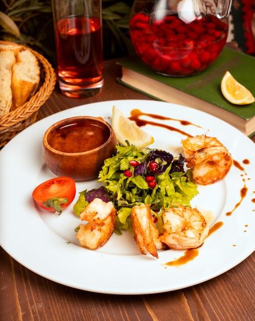 Gegrillte spalten mit grünem salat, tomaten, zitrone und dip-sauce in weißen teller. Kostenlose Fotos