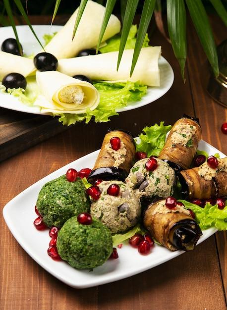 Gegrillte zucchini, auberginen, brokkoliröllchen gefüllt mit frischkäse, essiggurken, kapern und kräutern, granatapfelkernen Kostenlose Fotos