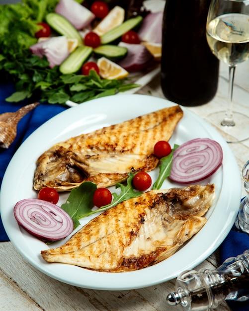 Gegrillter fisch in der hälfte, serviert mit zwiebeln und kirschtomaten Kostenlose Fotos