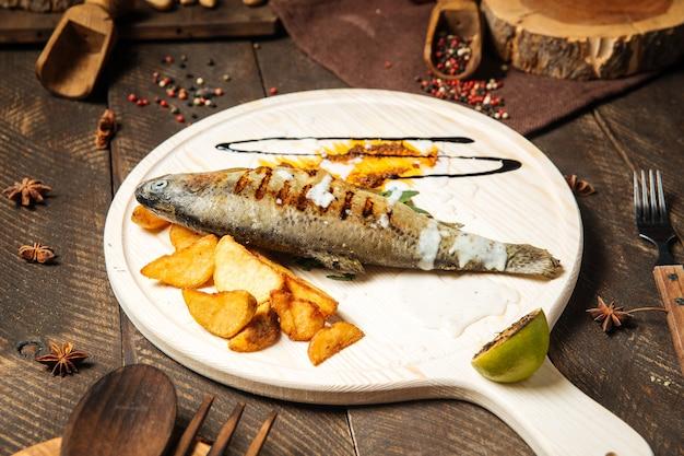 Gegrillter fisch mit kartoffeln auf dem holzbrett Premium Fotos