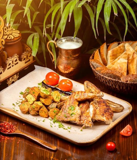 Gegrillter gebratener brathähnchentabak auf weißer platte mit kartoffel auf küchentisch Kostenlose Fotos