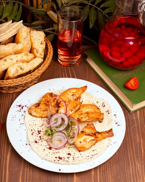 Gegrillter hühnerflügelkebab diente mit kompost, zwiebelgemüsesalat und kräutern in der weißen platte Kostenlose Fotos
