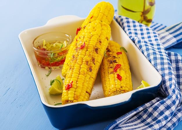 Gegrillter zuckermais mit mexikanischer soße, paprikas und kalk auf blauem hintergrund. Premium Fotos