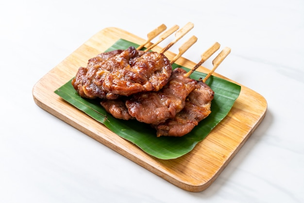 Gegrilltes aufgespießtes milchschweinefleisch mit weißem klebrigem reis Premium Fotos