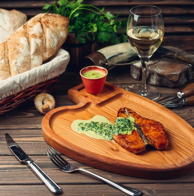 Gegrilltes fischfilet mit cremiger kräutersauce und einem glas weißwein. Kostenlose Fotos