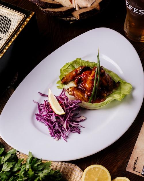 Gegrilltes fleisch in teriyaki-sauce in salatblatt mit rotkohlsalat und zitrone. Kostenlose Fotos