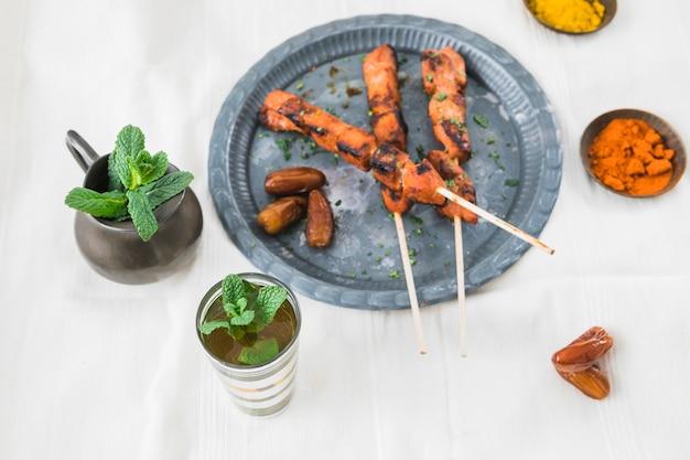 Gegrilltes fleisch mit trockenpflaumen in der nähe von tasse, gewürzen und krug Kostenlose Fotos