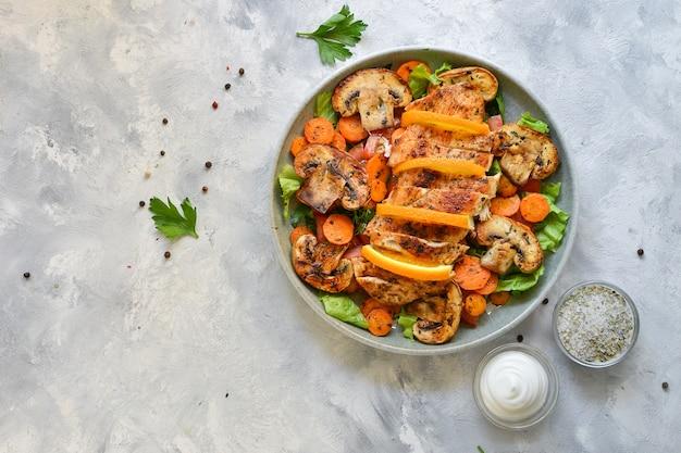 Gegrilltes gemüse und hähnchenbrustsalat. hühnerbrust, salat, pilze, tomaten, orange. Premium Fotos