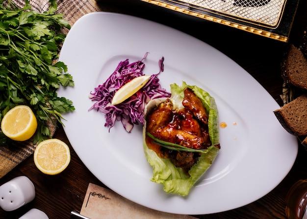 Gegrilltes hähnchen in teriyaki-sauce mit rotem cabbahe, kräutern und zitrone. Kostenlose Fotos